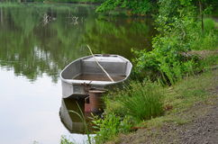 Old metal boat on the shore of the pond Royalty Free Stock Image