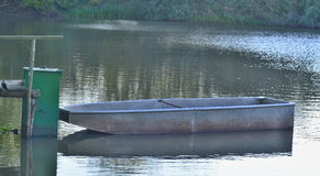 Old metal boat on the shore of the pond Royalty Free Stock Photo