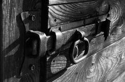 Old metal lock in black and white. Old metal bolt of a wooden gate - old wooden door Royalty Free Stock Image