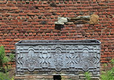 Old metal box in front of weathered brick wall Stock Photo