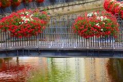 Old metal bridge. Metal bridge  on stream Leuk ( too Leukbach ) and geranium flowers in Saarburg, Rheinland-Pfalz, Germany, summer Royalty Free Stock Images