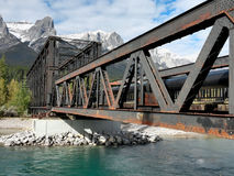 Old metal railroad bridge in canadian rockies. Old railroad bridge spans the Bow River in town of Canmore, province of Alberta Canada. Taken after 1st snow of Stock Photo