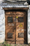 Old metal brown doors of old white brick building of transformer Royalty Free Stock Photos