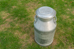 Old metal can on milk on green yard Stock Photos