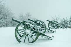 Old metal cannons covered with snow stock photography