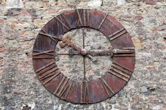 Old metal clock. An image of a very old metal clock with roman numerals mounted on a brick wall Stock Images