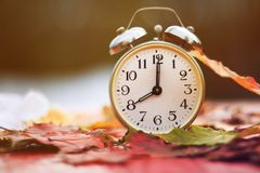 Old metal clock standing on a red wooden table amongst fallen au Royalty Free Stock Photo