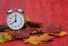 Old metal clock standing on a red wooden table amongst fallen au Stock Photography