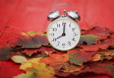 Old metal clock standing on a wooden table amongst fallen autumn Royalty Free Stock Photography