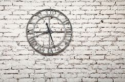 Old metal clock on white painted grunge brick wall. Close up old vintage retro style metal wall clock over background of white painted grunge brick wall Stock Image