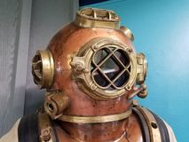 Old metal diving suit with helmet and glass window stock image