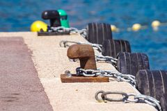 Old metal dock mooring pole with ring and rope for securing fishing boats.  Stock Images