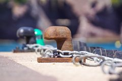Old metal dock mooring pole with ring and rope for securing fishing boats.  Stock Photos