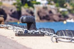 Old metal dock mooring pole with ring and rope for securing fishing boats.  Stock Image