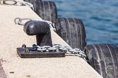 Old metal dock mooring pole with ring and rope for securing fishing boats.  Royalty Free Stock Images