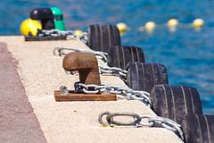 Old metal dock mooring pole with ring and rope for securing fishing boats.  Royalty Free Stock Photography