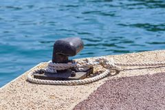 Old metal dock mooring pole with ring and rope for securing fishing boats.  Royalty Free Stock Image
