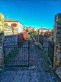 Old metal door accessing a street. Old metal access door to an unpaved street stock photo