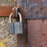 Old metal door closed with a lock Stock Photos