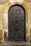 Old metal door are established in a sandstone wall, beautifully Royalty Free Stock Photos