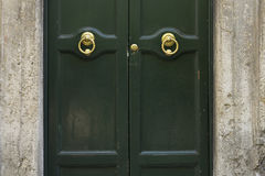 Old metal door handle on a green wooden door. Art work. Rome, It Stock Photo