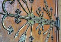 Old metal door hinge on a wooden door. Old metal door hinge on a vintage European wooden door stock photos