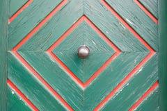 Old metal door knob on a wooden door Royalty Free Stock Image