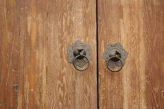 Old metal door knockers. Two metals knockers on wooden door of old Chinese house or home Stock Photos