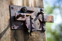A really old metal door lock on a wooden door royalty free stock photo