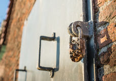 Old metal door locked with an weathered padlock Royalty Free Stock Photo