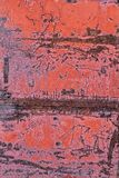 Old metal door with peeling red paint. Rusty scratched metal surface stock images
