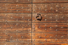 Old metal doorknocker on the wooden gate fixed with rivets Royalty Free Stock Photos
