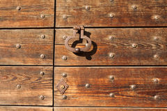 Old metal doorknocker on the wooden gate fixed with rivets Stock Images
