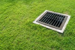 Old metal drain on green lawn. In the park stock photo