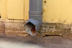 Drainpipe on the yellow wall of the house royalty free stock images