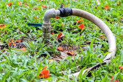 Old metal faucet and rubber tube that goes from metal pipe Royalty Free Stock Photos