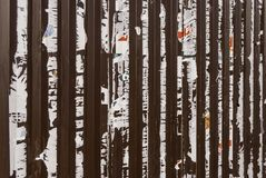 Old metal fence with the remains of previously pasted ads on it. royalty free stock photo