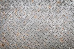 Old metal floor plate with diamond pattern and rusty background Stock Image