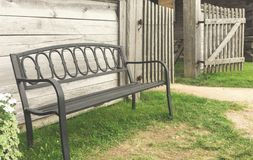 Old metal forged bench near a wooden wall royalty free stock photos