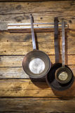 Old metal frying pans hanging on wooden wall Stock Photography