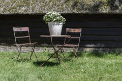 Old metal furniture in garden. Old red metal chairs and table in garden in front of farm Royalty Free Stock Photos