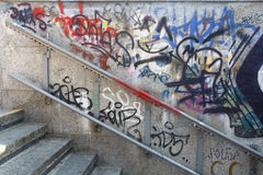 Old metal handrail on a wall with graffiti Stock Image