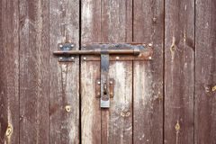 Old metal hasp on old wooden door. Stock Photos
