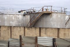 Old metal industrial storage tanks with rusty inspection ladders and valves surrounded by a corrugated steel fence and wall royalty free stock photo