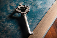 Old metal key on antique book. Stock Image