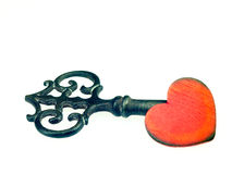 Old metal key and red heart. Royalty Free Stock Image