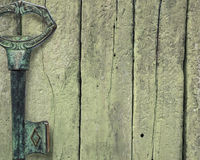 Old metal key on wooden background Stock Photo