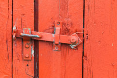Old metal latch on red wooden door. Close-up photo Stock Photos