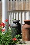Old metal milk jugs on wood stoop Royalty Free Stock Photos