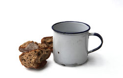 Old metal mug and bread. Old metal cup and hunks of brown bread with white studio background Stock Image